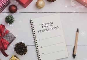 2018 resolutions on Note book and pen with Christmas and New Year holidays gift box with decorative ornament on wooden table.Gifts and congratulations concept.
